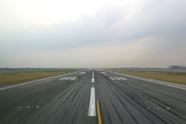 Startbaan van vliegveld in de avond met geopend lichtsysteem.