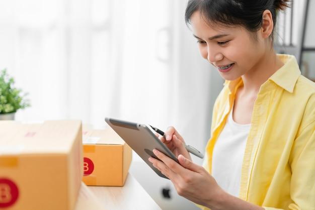 Startend klein bedrijf, een jonge aziatische vrouw die online orde op digitale laptop en verpakkingsdozen controleert