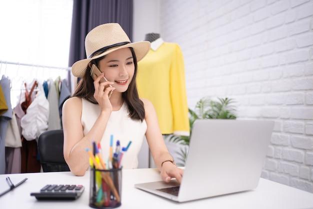 Startende kleine ondernemer kmo, aziatische vrouw die lacht om vragen van klanten te beantwoorden.