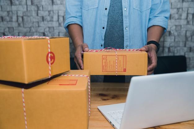 Startende kleine onderneming ondernemer sme of freelance aziatische man aan het werk met doos thuis c