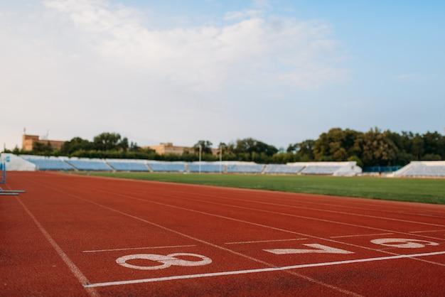 Startlijn voor hardlopen op stadion, niemand, vooraanzicht. lege loopband met cijfers, blessurebestendige coating, joggingoppervlak op sportarena