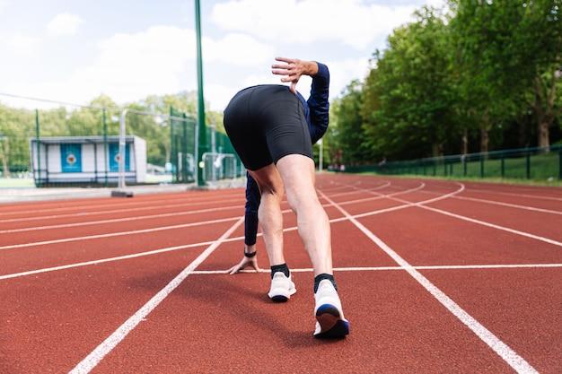 Startpositie op een atletiekbaan vanaf zijn rug tijdens gewichtsverlies in de lente