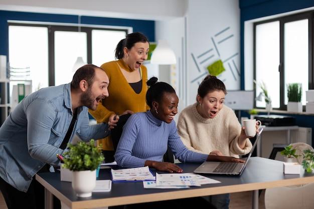 Startup diversiteitsteam viert feest na ondertekening van overeenkomst met belangrijke klant, partnerschap kijkend naar laptop. vrolijk multi-etnisch business team met laptop en papieren enthousiast over project.