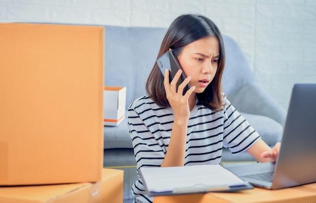 Startup klein bedrijf concept, jonge aziatische vrouw eigenaar praten op de smartphone met klanten over het bestellen van producten, verkoper bereidt de bezorgdoos.