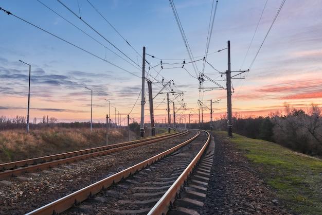 Station tegen mooie hemel bij zonsondergang. industrieel landschap met spoorweg en kleurrijke bewolkte blauwe hemel.