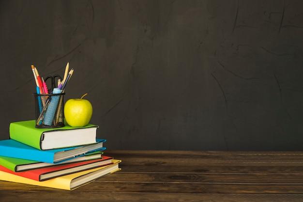 Stationair en appel op stapel boeken aan tafel