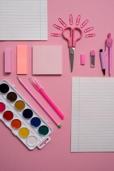 Stationair, plat bovenaanzicht foto van schaar, potloden, paperclips, rekenmachine, notitie, nietmachine en notitieblok in roze en blauwe tint op roze achtergrond met copyspace.