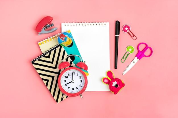 Stationair, terug naar school en onderwijsconcept schoolbenodigdheden op roze, plat liggen