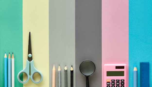 Stationaire items op pastel kleur papier achtergrond, terug naar school plat lag concept