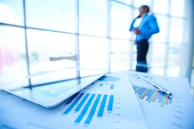 Statistiek documenten met zakenman onscherpe achtergrond