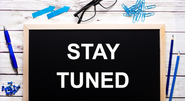 Stay tuned geschreven op een zwart notitiebord naast blauwe paperclips, potloden en een pen