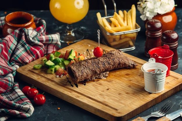 Steak roll geserveerd met komkommer, tomaat, dille en olijfolie salade
