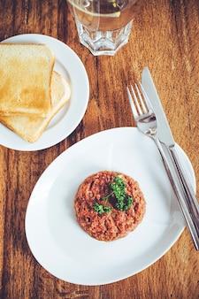 Steak tartaar gemaakt van rauw rundvlees in blokjes gesneden en gekruid. houten tafel achtergrond.