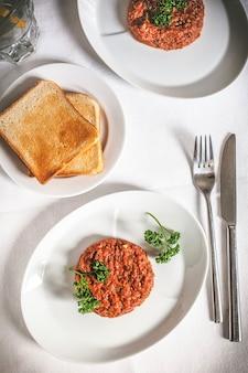 Steak tartaar gemaakt van rauw rundvlees in blokjes gesneden en gekruid. witte tafel doek achtergrond.