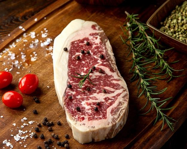 Steak vlees rozemarijn tomaat peper zijaanzicht