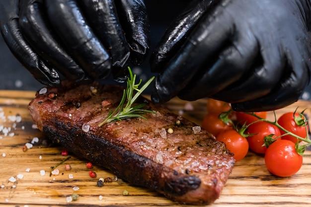 Steakhouse-menu. biefstuk van de lendenen. close-up van chef-kokhanden die geroosterd rundvlees met kersentomaten en rozemarijntakje dienen.