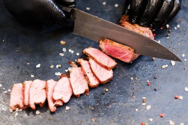 Steakhouse-menu. biefstuk van de lendenen. close-up van chef-kokhanden die middelgroot zeldzaam geroosterd rundvleesvlees snijden.