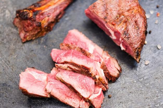 Steakhouse-menu. cowboybiefstuk. bovenaanzicht close-up van gesneden gegrild rundvlees en bot.