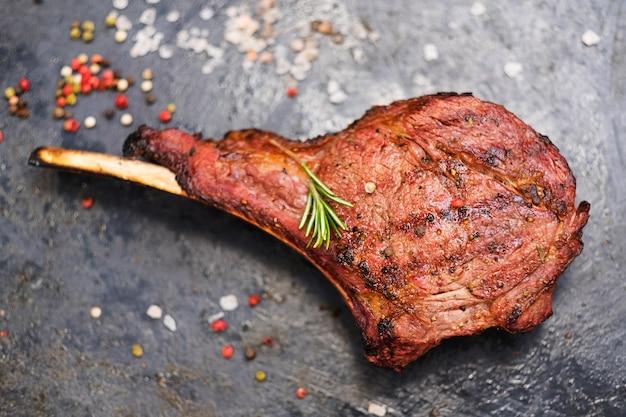 Steakhouse-menu. cowboybiefstuk. bovenaanzicht van gegrild bot in rundvlees geserveerd met kruiden en rozemarijntakje.