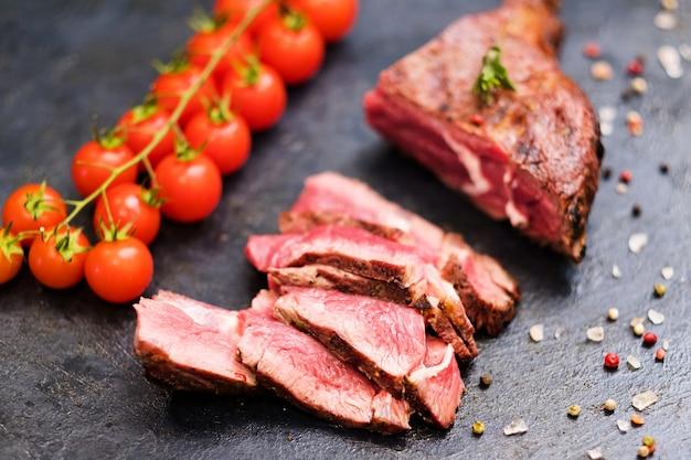 Steakhouse-menu. cowboybiefstuk. gesneden medium gegrild rundvlees, cherrytomaatjes en mengsel van paprika's.