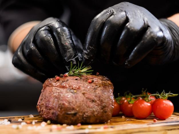 Steakhouse-menu. ossenhaas biefstuk. chef-kok handen serveren gegrild rundvlees met kerstomaatjes en rozemarijn takje.