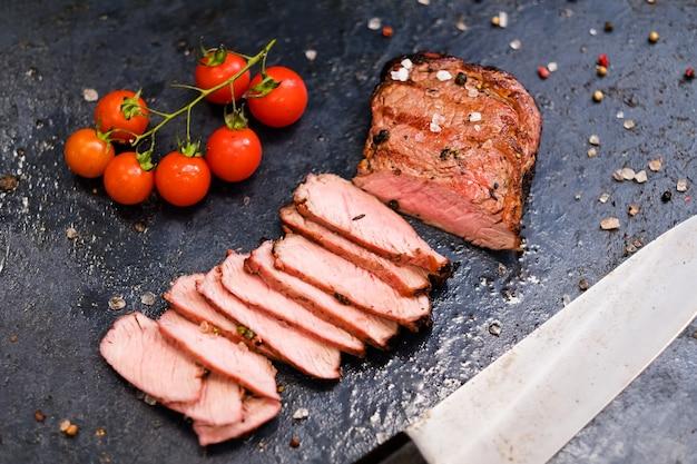 Steakhouse-menu. rib eye steak. bovenaanzicht van gesneden medium gegrild rundvlees, cherrytomaatjes, mengsel van paprika en mes.