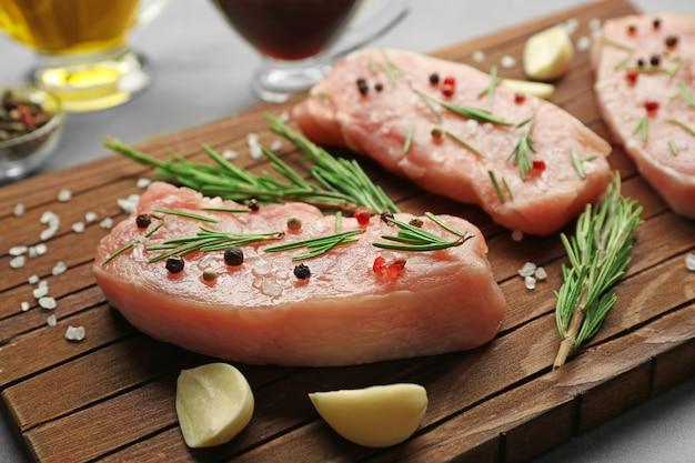 Steaks in marinade op een houten bord, close-up