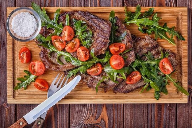 Steaks met rucola en tomaten.