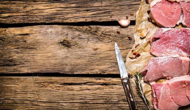 Steaks van rauw vlees met kruiden op de houten achtergrond