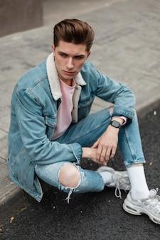 Stedelijk jongemanmodel met kapsel in modieus blauw spijkerjack in stijlvolle gescheurde spijkerbroek in witte schoenen rusten op tegels in de buurt van de weg. lieve kerel in casual jeugdkleding op straat in de stad. zomerse stijl.