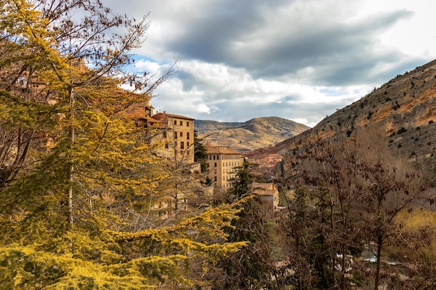 Stedelijk landschap in de herfst met grote roodachtige bomen en oude stenen huizen. albarracin teruel spanje. europa.