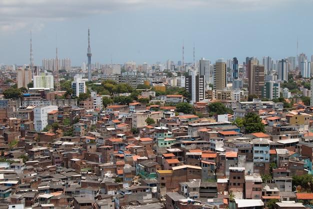 Stedelijk landschap met sociaal contrast tussen favela en gebouwen.