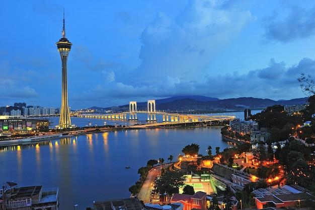 Stedelijk landschap van macau met beroemde reizende toren onder blauwe hemel dichtbij rivier in macao, azië.