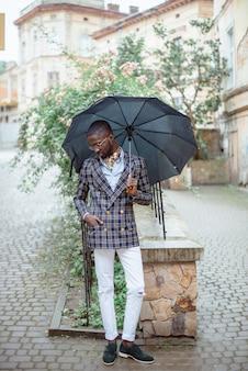 Stedelijk portret van knappe afro-amerikaanse zakenman permanent in het centrum van de stad bij bewolkt weer onder zwarte paraplu gekleed in formele kleding.