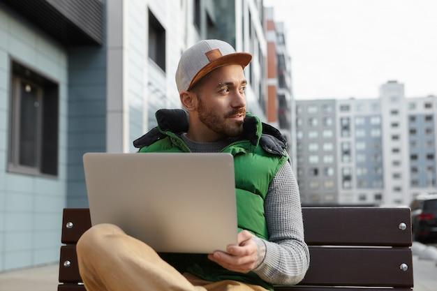 Stedelijk portret van knappe stoppels jonge europese kerel op afstand zittend op een bankje met draagbare computer op zijn schoot tegen wazig gebouwen, zijwaarts op zoek en glimlachen