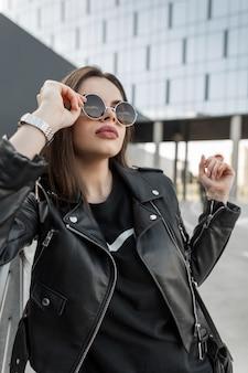 Stedelijk portret van modevrouw in stijlvolle zwarte kleding met leren jas en jurk zet een modieuze zonnebril op in de moderne stad