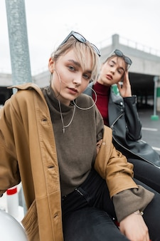 Stedelijk portret van mooie jonge vrouwen met leren jas en trui in zwarte spijkerbroek zit en poseert op straat