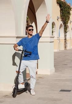 Stedelijk vervoer. gelukkige jonge kerel in vrijetijdskleding met behulp van elektrische duwscooter op straat in de stad, zwaaiend naar iemand, groet vriend buitenshuis, kopieer ruimte. actieve vrije tijd, zomersportconcept