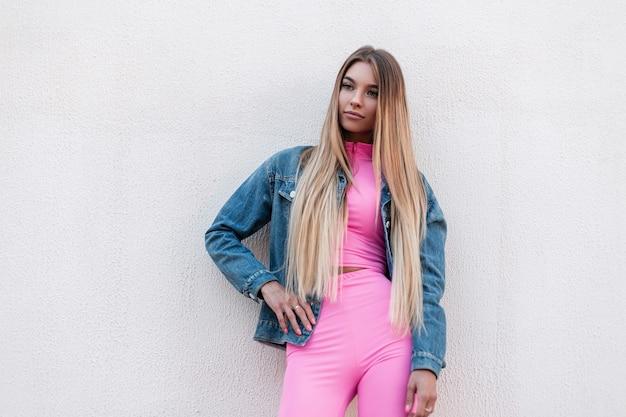 Stedelijke aantrekkelijke jonge vrouw blond met lang haar in roze stijlvolle korte broek in een roze top in een trendy denim jasje staat in de stad in de buurt van een vintage gebouw op een zomerdag. mooi stijlvol meisje