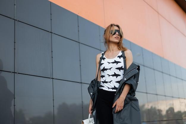 Stedelijke aantrekkelijke jonge vrouw in stijlvolle kleding in vintage zonnebril met een rugzak vormt in een stad in de buurt van een modern grijs gebouw. trendy roodharige meisjesmodel geniet van een zonnige dag.