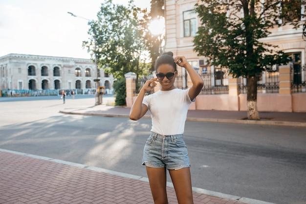 Stedelijke afro amerikaanse vrouw die op het vierkant van de stadsstraat op zonsondergang lopen