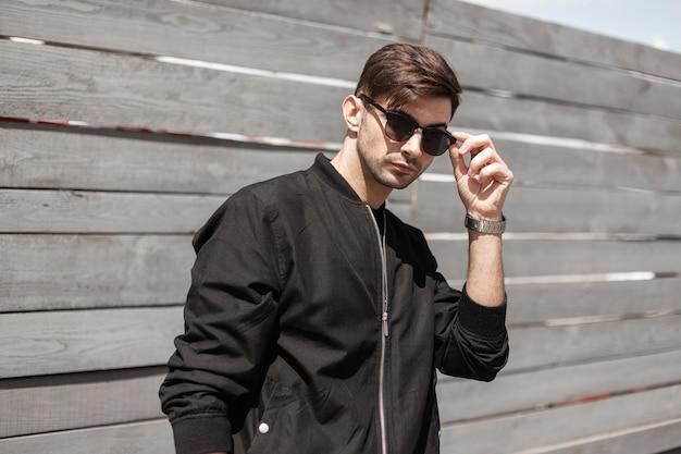 Stedelijke amerikaanse jongeman in een stijlvolle zwarte jas staat en trendy zonnebril rechtzetten in de buurt van een houten hek op een zonnige zomerdag. knappe kerel brunette buitenshuis.