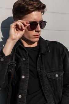 Stedelijke amerikaanse man mannequin zet vintage zonnebril op straat in zonnige dag