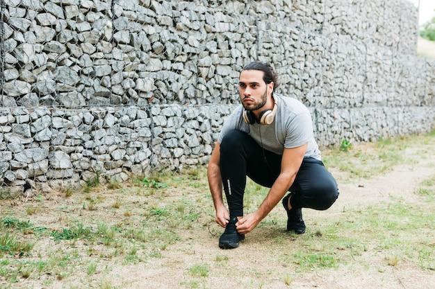Stedelijke atleet die schoenen vastmaakt