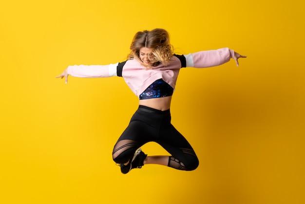 Stedelijke ballerina die over geïsoleerd geel dansen en springen