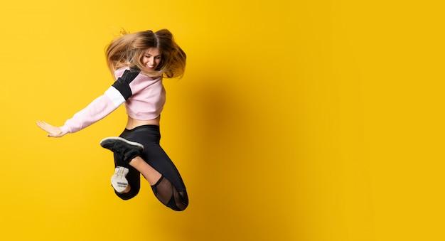 Stedelijke ballerina die over geïsoleerde gele achtergrond en het springen danst