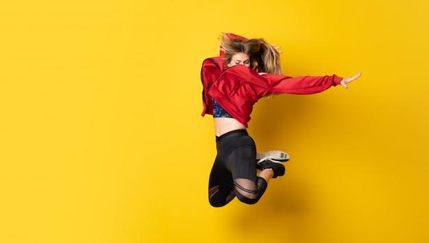 Stedelijke ballerina die over geïsoleerde gele muur en het springen danst