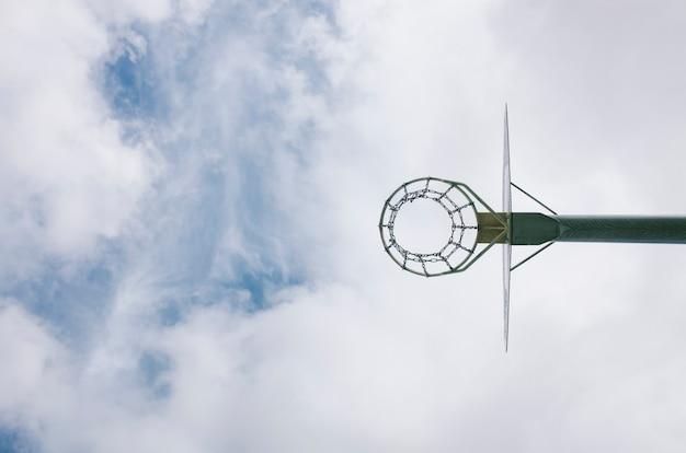 Stedelijke basketbalmand met een blauwe hemel