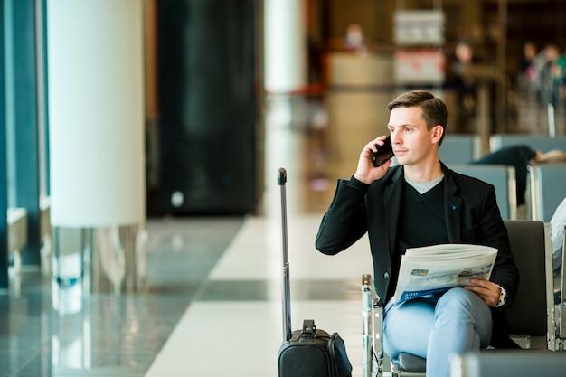 Stedelijke bedrijfsmens die op slimme telefoon binnen in luchthaven spreekt.
