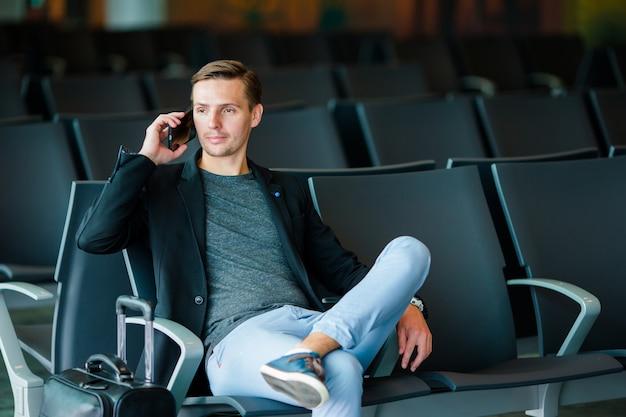 Stedelijke bedrijfsmens die op slimme telefoon spreekt die binnen in luchthaven reist. jonge man met mobiel op de luchthaven wachten op instappen.